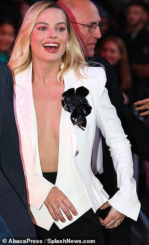 Sexy: Margot's smartly tailored vest was so low cut, in fact, that the waist of her roomy black slacks peeked out from above the vest's buttons