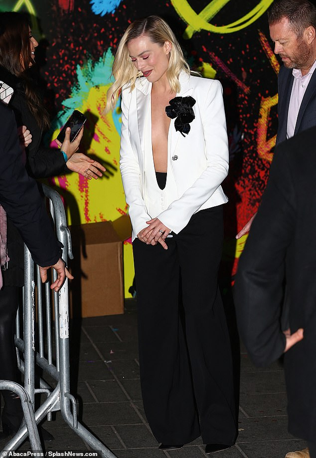 Black-and-white stunning:Robbie, 29, wowed in a chic yet quite risque white blazer and vest set, with a precipitous bust line and no top underneath