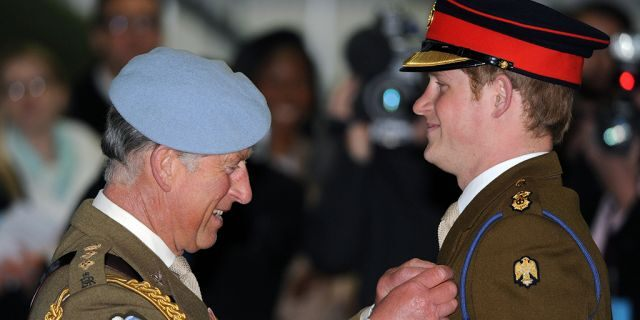 Prince Charles, Prince of Wales presents Prince Harry with his flying wings and his Army Flying Corps blue beret at Prince Harry's pilot course graduation at the Army Aviation Centre on May 7, 2010, in Andover, England.