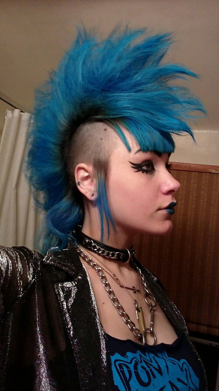 extravagant punk Mohawk styled to look like a cock and shaded blue. The sides are faded and remain black
