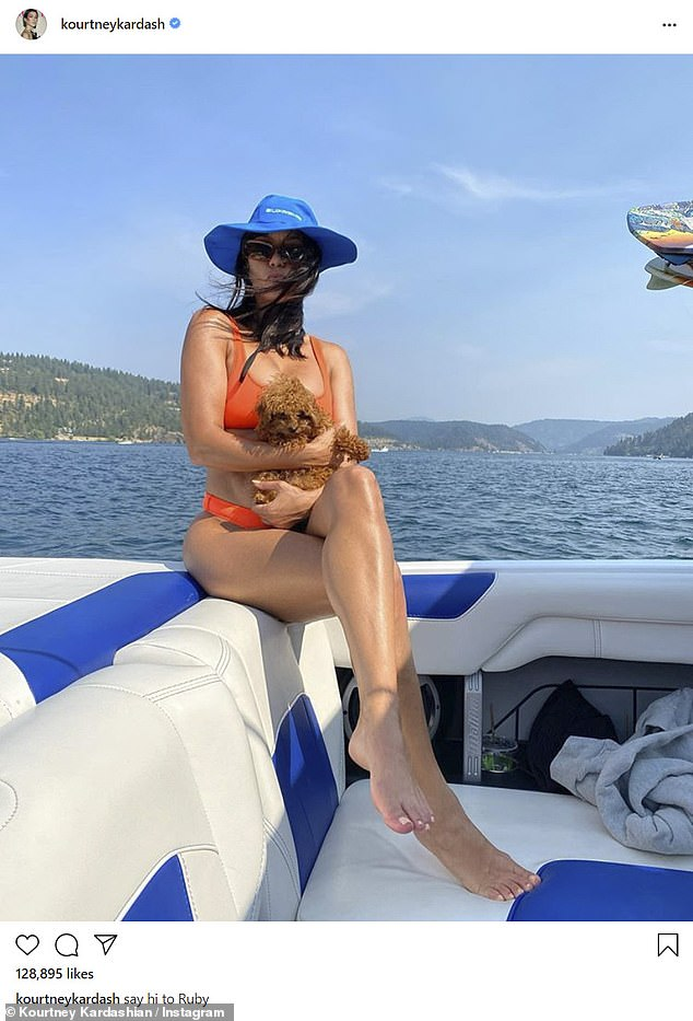 Bikini babe: Reality star Kourtney, 41, looked incredible in an orange bikini as she hit the high seas with her new poodle puppy, Ruby.